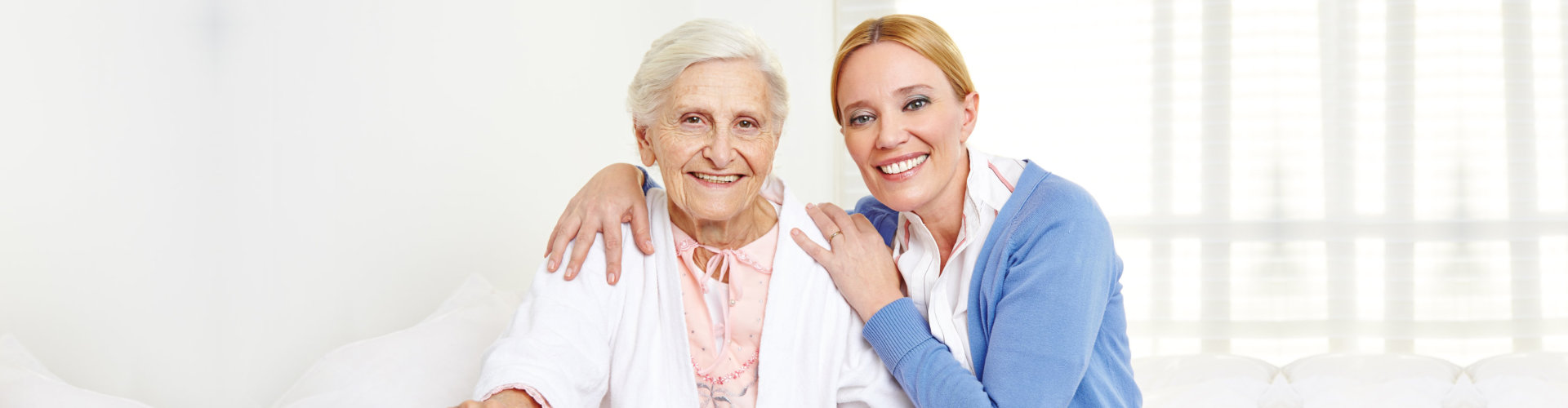 smiling caregiver and her old woman patient